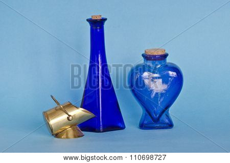 Two Blue Glass Bottles With Decorative Brass Object