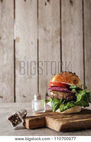 Homemade Veggie Burger In A Bun With Sesame Seeds Of Beer. Delicious Fast Food For Vegans. On A Wood