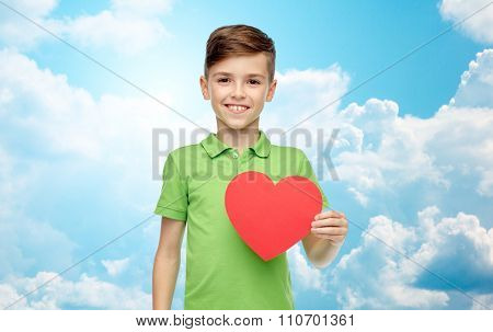 childhood, love, charity, health care and people concept - happy smiling boy in green polo t-shirt holding blank red heart shape over blue sky and clouds background