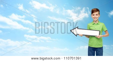 childhood, direction, advertisement and people concept - happy smiling boy in green polo t-shirt holding white blank arrow banner over blue sky and clouds background