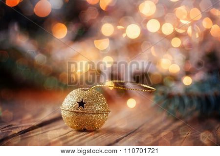 Gold Metal Jingle Bell With Star On Wooden Table With Boke And G