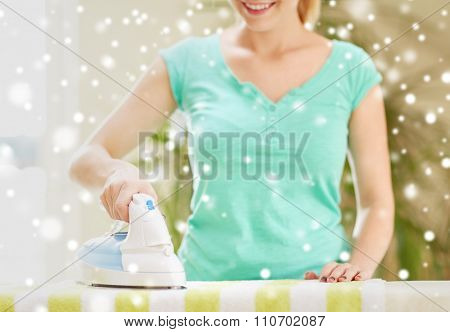 people, housework, laundry and housekeeping concept - close up of happy woman with iron and ironing board at home over snow effect
