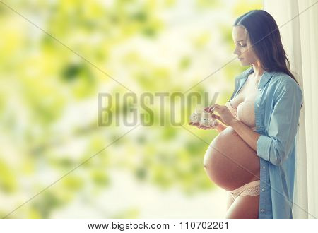 pregnancy, motherhood, people and expectation concept - happy pregnant woman with big bare tummy holding little baby booties at home over green natural background