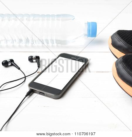 fitness equipment : running shoes drinking water phone and ear phone on white wood table