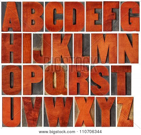 complete English alphabet set - a collage of 26 isolated vintage wood letterpress printing blocks, scratched and stained by red ink , gothic bold extended font