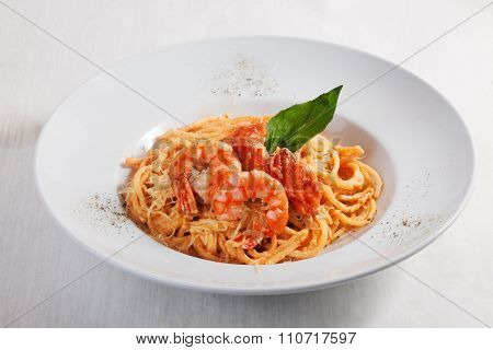 pasta with shrimp and salmon isolated on white background tomato sauce Round plate menu