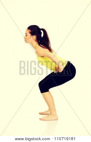 Attractive fitness woman performs squats.