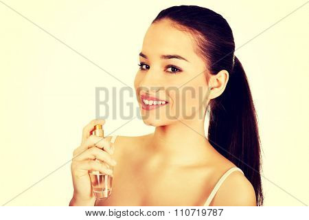 Young beautiful woman applying parfume.
