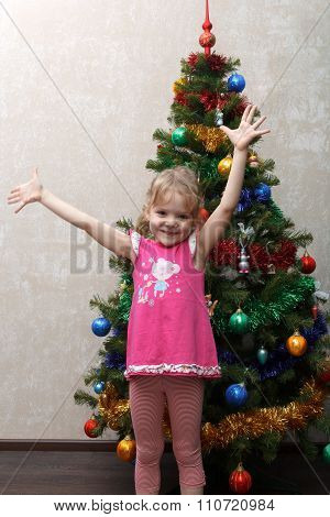 Little Girl Rejoices And Jumps Near Christmas Tree