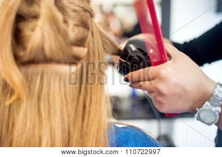 Blonde Woman At Hair Salon Using A Professional Tool For Creating Curls With Long Lasting Effect