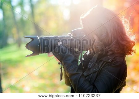 A Professional Cute Woman Photographer Taking Outdoor Pictures With Camera During Sunset