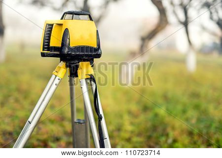 Surveying Measuring Equipment Level Theodolite On Tripod On A Foggy Day In Construction Site