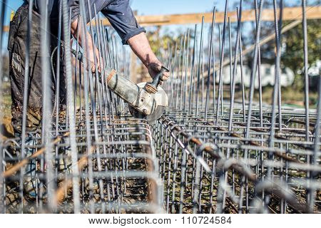 Worker Using An Angle Grinder To Cut Steel Bars Used For Reinforcement At Construction Site