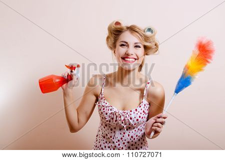 Pretty girl in curlers with red spray and rainbow duster
