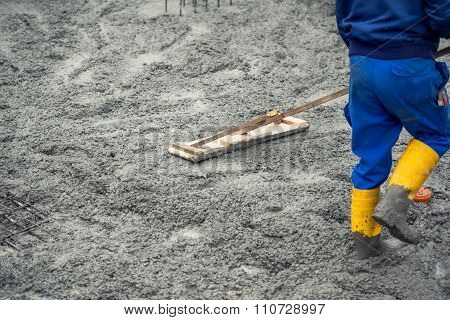 Worker Leveling With Wooden Trowel The Fresh Poured Concrete Or Cement At Construction Site