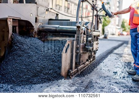Worker Or Engineer Operating An Ashphalt Paving Machine At Road construction