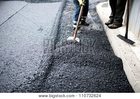 Worker With Shovel Doing Manual Labor At Road Construction With asphalt