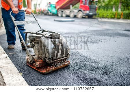 Asphalt Worker At Road Repairing And Construction Site With Manual compactor plate