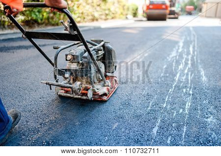 Road Construction With Worker Paving The Fresh Bitumen Or Asphalt