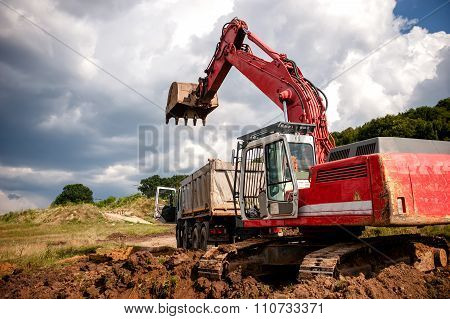 Heavy Bulldozer And Excavator Loading And Moving Red Sand Or Soil on road construction site