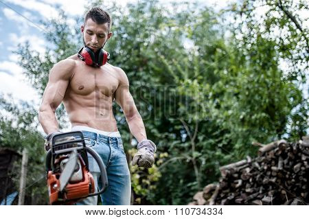 Portrait Of Sexy Man With Chainsaw And Protective Gear Ready For