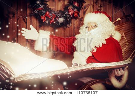 Santa Claus reading magic book in his wooden house. The magic of Christmas. Sepia.