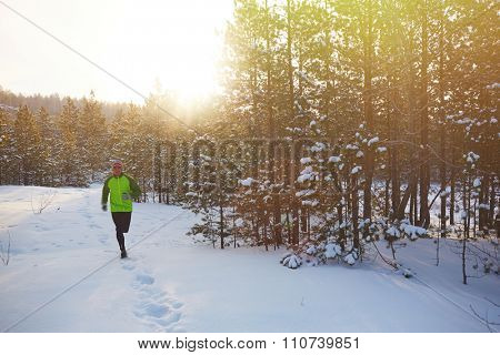 Young sportsman running in the forest in winter