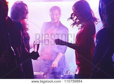Happy deejay looking at camera among dancing girls