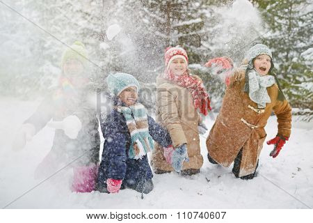 Happy children in winter-wear playing snowballs in park