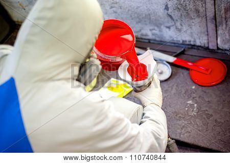 Auto Mechanic Mixing And Pouring Red Paint For Spraying And Painting cars