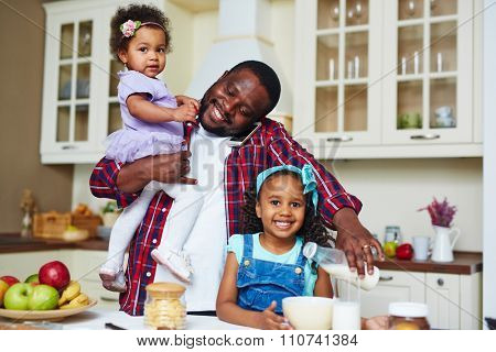 Happy African-American man making breakfast for his daughters