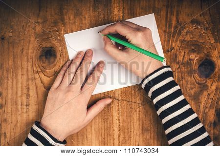 Woman Writing Sender Address On Mailing Envelope