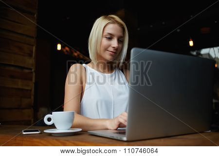 Beautiful blonde woman working on laptop computer during coffee break in cafe bar