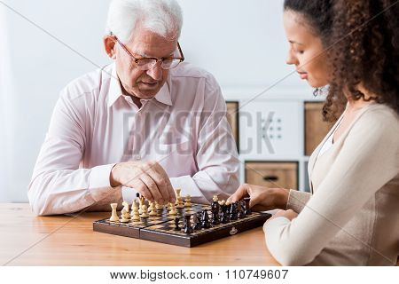 Retiree And Caregiver Playing Chess