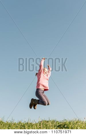 Jumping girl in front of blue sky