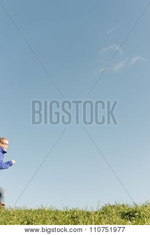 Girl running in front of blue sky