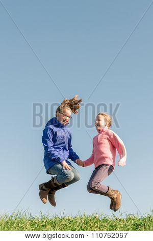 Jumping girls in front of blue sky