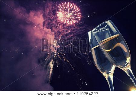 Glasses with champagne against night sky with fireworks