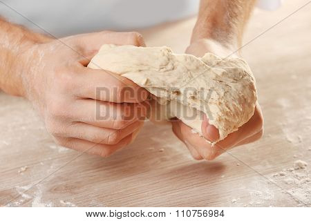 Hands kneading dough for pizza on the wooden table, close-up