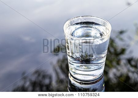 Refreshing Water In Transparent Glass With Reflection Against Blue Sky