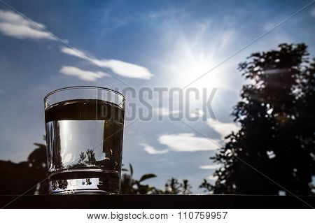 Silhouette Of Water In Transparent Glass Against Sky And Sun