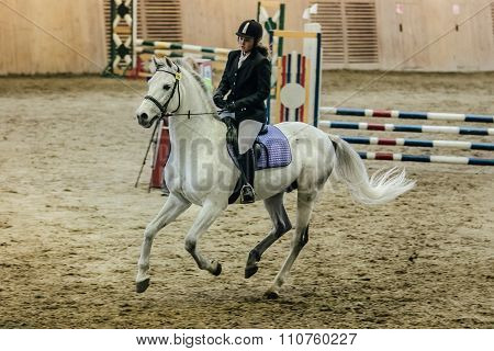 young girl athlete on a horse across field at sports complex