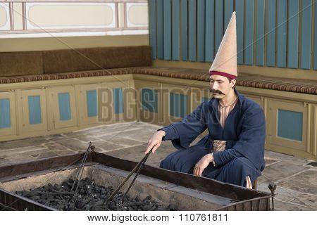 Zuluflu Guard (Zuluflu Baltaci)heating up a brazier inside Topkapi Palace, Istanbul, Turkey