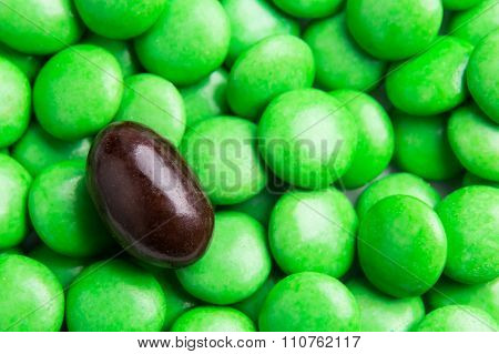 Focus On Brown Chocolate Candy Against Heaps Of Green Candies