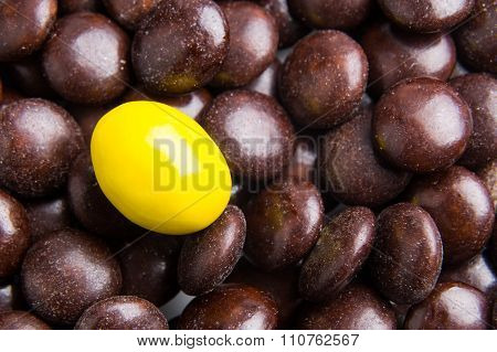 Focus On Yellow Chocolate Candy Against Heaps Of Brown Candies