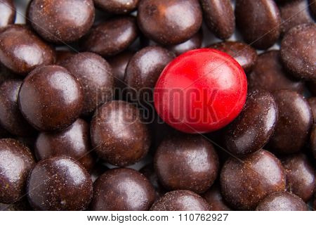 Focus On Red Chocolate Candy Against Heaps Of Brown Candies