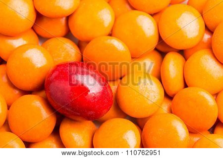 Focus On Red Chocolate Candy Against Heaps Of Orange Candies