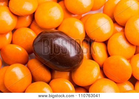 Focus On Brown Chocolate Candy Against Heaps Of Orange Candies