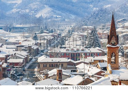 View of belfry and small town covered with snow in Piedmont, Northern Italy.