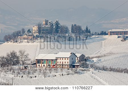 Rural houses on snowy hills of Piedmont, Northern Italy.
